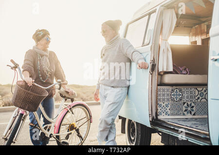 Happy people senior age couple smile and enjoy outdoor travel leisure activity together with vintage bike and van for alternative summer vacation conc - Stock Photo