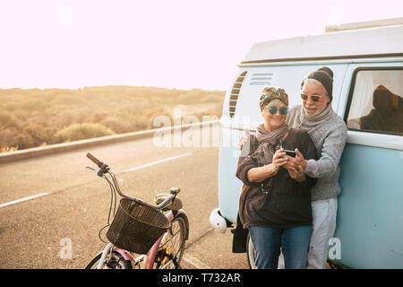 Travel and alternative old caucasian people couple concept with man and woman together looking a phone and enjoy the outdoor trip activity - happy sen - Stock Photo