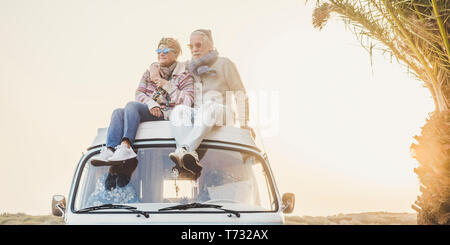 Wanderlust and travel destination happiness concept with old senior beautiful couple sitting and enjoying the outdoor freedom on the roof of vintage v - Stock Photo