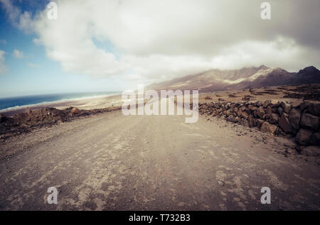 Long off road terrain way road viewed from ground level with mountains and coastline ocean view - travel and adventure concept for alternative vacatio