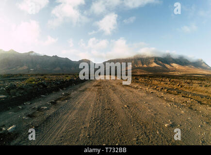 Long off road terrain way road viewed from ground level with mountains and blue cloudy sky - travel and adventure concept for alternative vacation and
