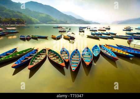 Amazing view on Phewa Lake. colorful boats queued at a midday.Province of Pokhara Nepal - Stock Photo