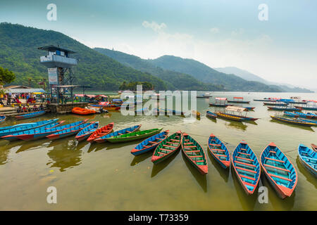 Amazing view on Phewa Lake. colorful boats stop at queued a midday 28-04-2019.in mid ground watch Tower and background green hills.Pokhara Nepal - Stock Photo