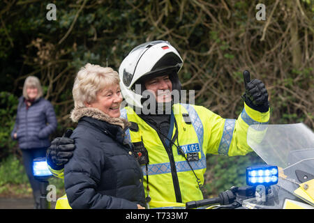 Police Motorcyclist wearing crash helmet and hi-vis Jacket posing for a photograph on the women's stage of The Tour de Yorkshire in Harrogate,UK. - Stock Photo