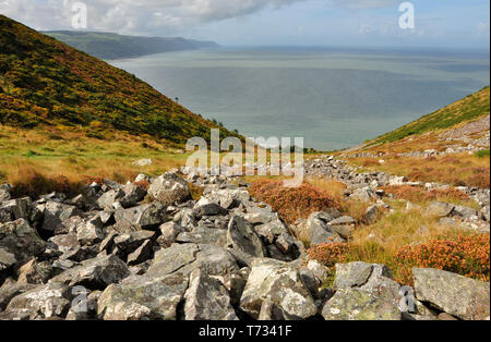 The rock strewn valley down which the South West coast path descends from Bossington Hill to Porlock Weir with a view across Porlock bay to the distan - Stock Photo