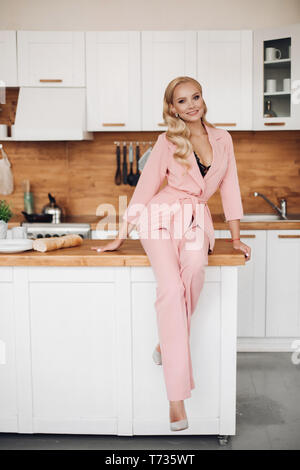 Gorgeous blonde woman in pink suit with loaf of bread on kitchen countrer. - Stock Photo