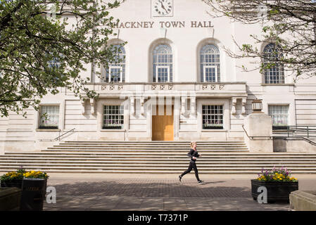 Hackney, London, England, UK - Facade of Hackney town hall with woman runner running in front of it