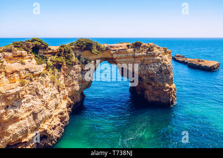 Natural arch above ocean, Arco de Albandeira, Algarve, Portugal. Stone arch at Praia de Albandeira, Lagoa, Algarve, Portugal. View of the natural arch - Stock Photo