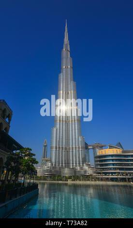 Dubai, United Arab Emirates - December 11, 2018. Burj Khalifa skyscraper view over the Dubai fountain from the Burj Park in sunny day. - Stock Photo
