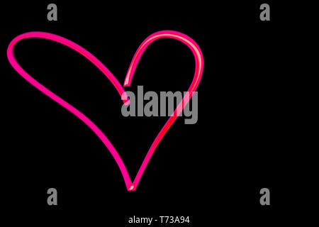 horizontal view of a pink heart outline light painting in black night sky