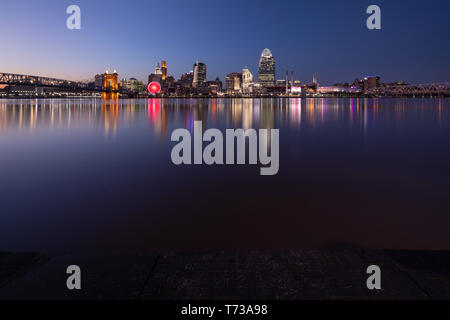 The sun sets in a clear blue sky over Cincinnati as city lights emerge from the buildings and the Ohio river smooths out on a cool Spring evening. - Stock Photo