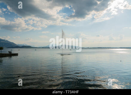 geyser and fountain in Lake Zug in Switzerland with a great mountain landscape view in the background - Stock Photo
