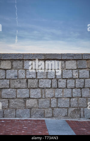 gray granite stone wall under a blue sky - Stock Photo