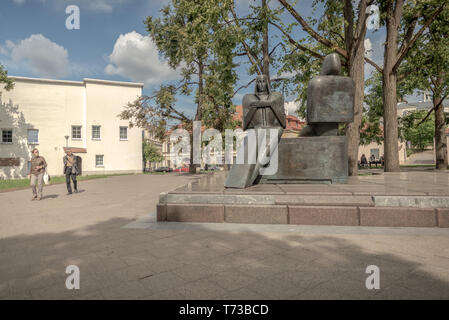 VILNIUS, LITHUANIA - JULY 7, 2018: Soviet era sculptures with two tourists looking at it in the historical center of Vilnius - Stock Photo