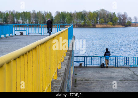 Kyiv region , Ukraine - April 21, 2019: A fishermen on quay of the Dnipro river in the city of Ukrainka, Kiev region, Ukraine - Stock Photo