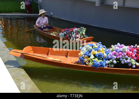 Milan/Italy - June 30, 2015: Woman sitting in traditional Thai wooden floating market boat filled with flowers anchored at Thailand Milano EXPO 2015. - Stock Photo