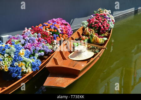 Milan/Italy - June 30, 2015: Two Thai wooden traditional boats for floating market filled with flowers anchored at Thailand Milano EXPO 2015 pavilion. - Stock Photo