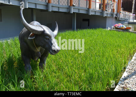 Milan/Italy - June 30, 2015: View to a green rice camp with sculpture of big horns ox standing on it at the Thailand pavilion of the EXPO Milano 2015. - Stock Photo