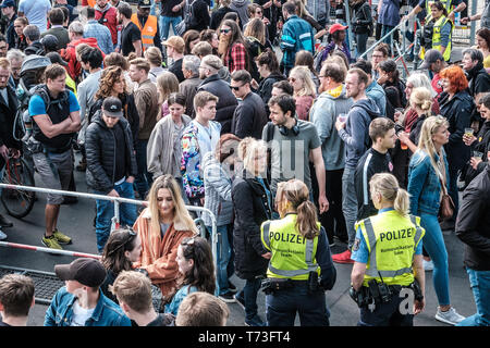 Berlin, Germany - May 01, 2019:  Many people and  police women at entrance to street fest on labor day in Berlin, Kreuzebrg - Stock Photo
