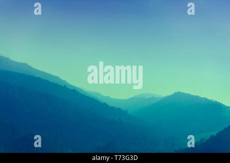 Mountain ranges in the early foggy morning. Sunrise over the mountains - Stock Photo