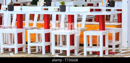 Row of colorful red, white and yellow tables and chairs in outdoor restaurant, cafe in Greece - Stock Photo