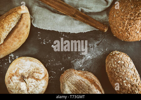 baked various loaves of bread on a black background, empty space in the middle, top view, vintage toning - Stock Photo