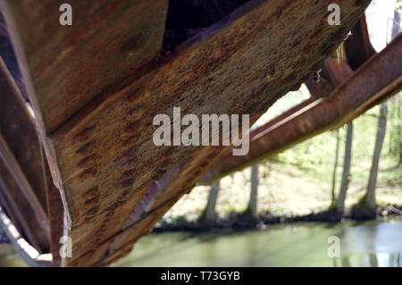 Old, rusty rivets. Corroded elements of the destroyed bridge. - Stock Photo