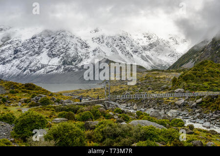 Snowy mountains and hanging bridge along the Hooker Valley Track, Mount Cook National Park; South Island, New Zealand - Stock Photo
