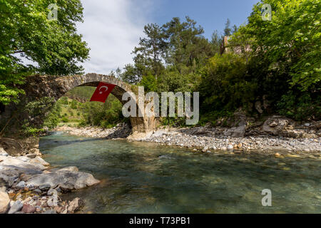 Old stone bridge over the mountain river with crystal clear water and the flag of Turkey hanging from that bridge - Stock Photo