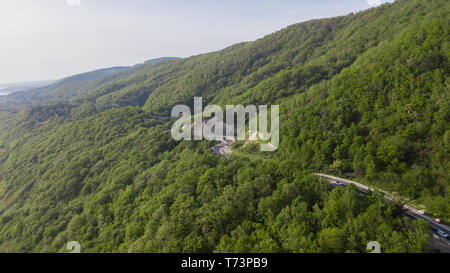 Curvy windy mountain road between green forest, top down aerial view. Summer landscape. - Stock Photo
