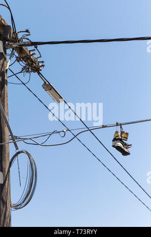 Sneakers hanging from telephone line exchange. - Stock Photo