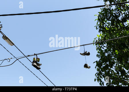 Two pairs of shoes hanging from telephone line above. - Stock Photo