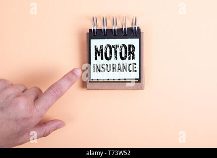 Motor Insurance concept. Woman's hand and note pad - Stock Photo