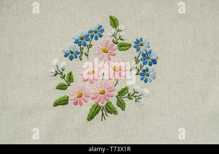 Embroidered bouquet of pink, blue and white flowers and green leaves on the background of cotton fabric - Stock Photo