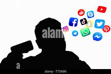 Petrozavodsk. Karelia. Russia. May 3. 2019: Social network icons fly out of a black man's profile with a smartphone in his hand on a white background - Stock Photo