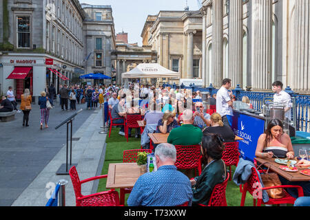 People eating at outdoor tables at a restaurant in Royal Exchange Square, Glasgow, Scotland - Stock Photo