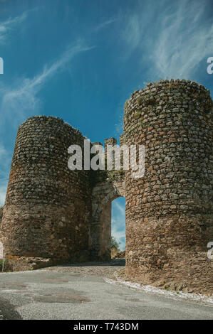 Stone thick towers beside the main entrance doorway on the outer wall of Evoramonte. A tiny fortified civil parish with an old castle in Portugal. - Stock Photo