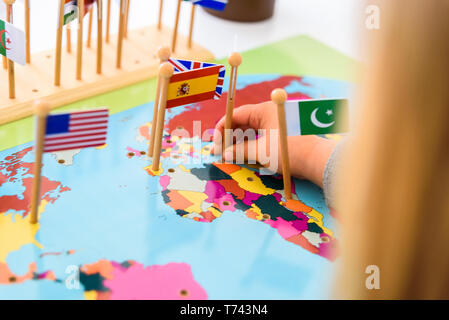 Geography exercise for children, place flags of countries on a map, flag of Spain. - Stock Photo