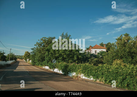 Countryside road on sunset and charming cottage amidst lush green trees near Elvas. A gracious city on the easternmost frontier of Portugal. - Stock Photo