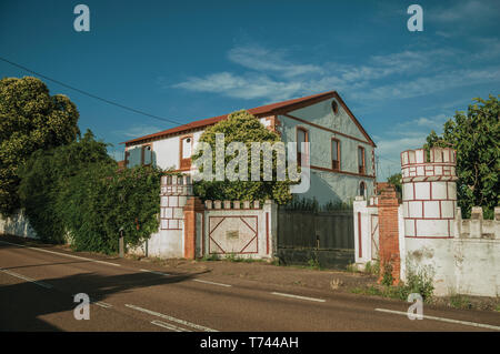Countryside road with gate and charming cottage amidst lush green trees, near Elvas. A gracious city on the easternmost frontier of Portugal. - Stock Photo