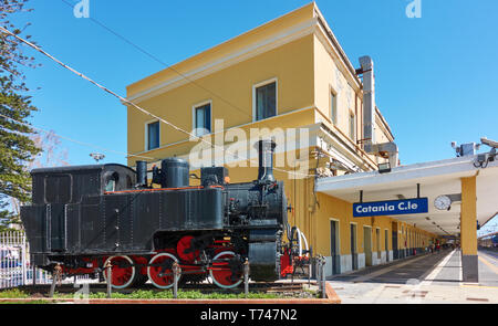 Catania, Italy - March 17, 2019: Old steam locomotive and building of main railroad station in Catania (Catania Centrale), Sicily, Italy - Stock Photo