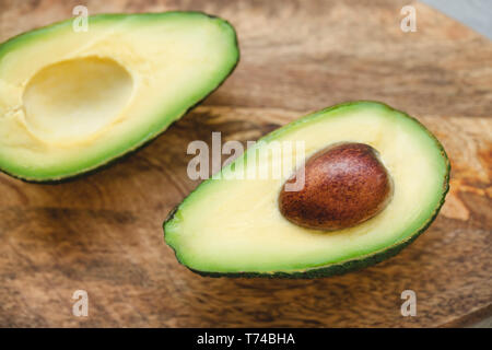 Two halves of fresh riped avocado on a wooden board. Close up, selective focus. - Stock Photo