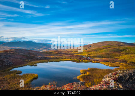A view from Peters Hills of the setting sun with parting clouds revealing 20,320' Mount McKinley with a unnamed lake in the foreground - Stock Photo