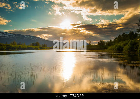 The calm waters on a unnamed lake in Portage Valley on a sunny, summer evening as the sun sets in South-central Alaska - Stock Photo