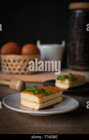 layer vanilla flavoured cake place on white plate on the wooden table there are black plate and coffee bean in glass bottles and bucket of water ceram - Stock Photo