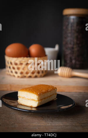 layer vanilla flavoured cake place on black plate on the wooden table there are coffee bean in glass bottles and bucket of water ceramic and basket of - Stock Photo