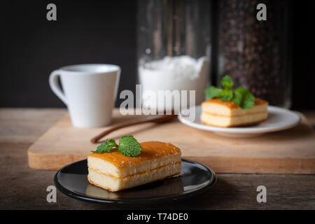 layer vanilla flavoured cake place on black plate on the wooden table there are white plate and coffee bean, flour in glass bottles and white cup and  - Stock Photo