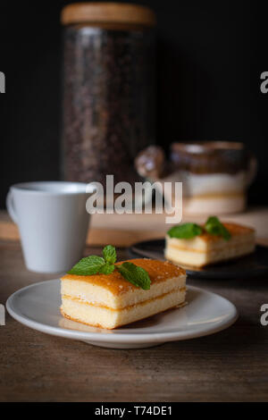 layer vanilla flavoured cake place on white plate on the wooden table there are white cup and black plate and coffee bean in glass bottles and waterin - Stock Photo