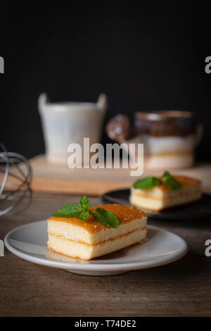 layer vanilla flavoured cake place on white plate on the wooden table there are black plate and  bucket of water ceramic and watering ceramic place ba - Stock Photo