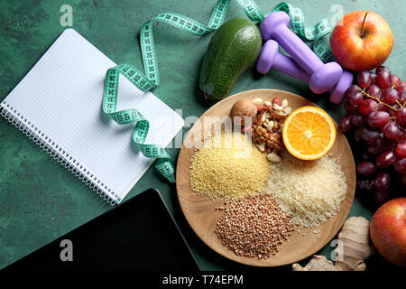 Wooden tray with healthy food and tablet PC on green background